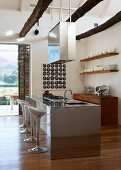 Open kitchen with designer barstools at stainless steel kitchen island, suspended extractor hood and white crockery on open wooden shelves