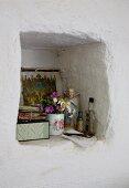 Posy of garden flowers in beaker and angel figurine in masonry wall niche