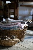 Basket of old objects in front of basket of laundry on floor