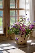 Spring bouquet in rustic jug on windowsill