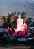 Advent arrangement of candles, pine cones and bird ornaments