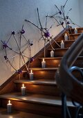 Twigs tied together to make snowflakes and candles as Christmas decorations on staircase