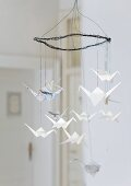 Wire mobile hung with origami cranes made from newspaper and writing paper