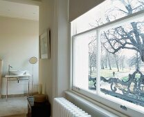 Modernised bedroom with ensuite bathroom and view of garden through window