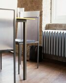 Metal designer chair in front of brick wall and window