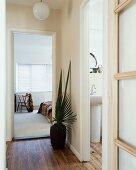 Floor vase with palm leaves next to open door showing view of bedroom