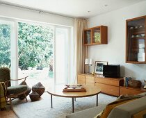 50s-style living room with floor to ceiling terrace windows and view of garden