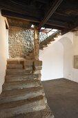 Rustikale Steintreppe im Vorraum eines mediterranen Landhauses