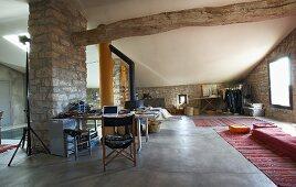 Offener Wohnraum mit Natursteinwänden in mediterranem Landhaus