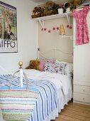 Girl's bedroom with iron bedstead below shelf of teddy bears