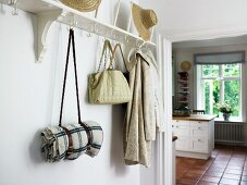 White coat rack with hooks in foyer and view into kitchen