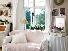 Sofa with pink throw below window next to mirror and flower arrangement on side table