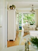 Classic, white, vintage furnishings in living room with view of large windows and balcony door