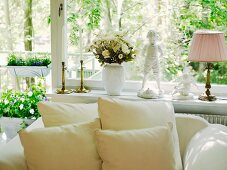 Cushions on white, upholstered armchair below large window decorated with flowers and vintage-style ornaments