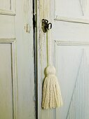Detail of lock on shabby chic, antique cupboard with simple tassel hanging from key