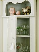 Glasses in romantic corner cupboard decorated with dolls' heads and floral potpourri