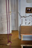 Swing suspended from ceiling and open door in rustic setting