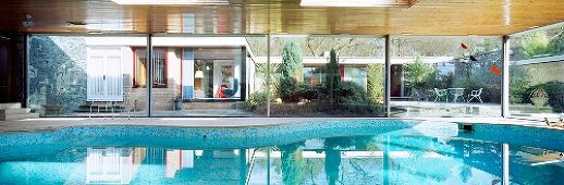 Spacious roofed swimming pool in front of modern bungalow