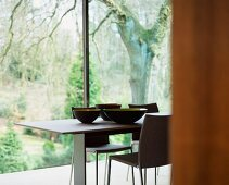 Set of designer bowls on table in front of floor-to-ceiling windows with view of garden