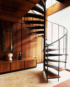 Open spiral staircase on tiled floor with sideboard in front of wood-panelled wall