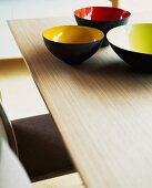 Set of coloured bowls on wooden table