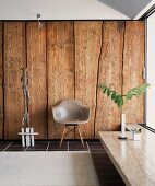 Classic chair with grey plastic shell seat in front of rustic wooden wall