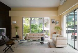 Living room with cream-coloured, Bauhaus-style sofas in front of large sliding windows