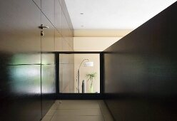 Gallery with door integrated in dark wood panelling and glass balustrade with view of living room below