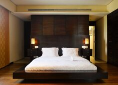 Floating double bed in front of dark wood partition