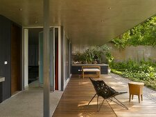 Metal armchair with fabric shell seat and side table on concrete-roofed terrace with wooden decking