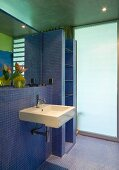 Built-in shelf and designer sink in bathroom with blue mosaic tiles and frosted glass wall