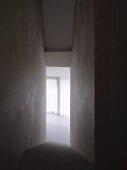 Schmaler, hoher Treppenabgang ohne Handlauf und Blick in sonnigen Raum mit Vorhang aus Vertikallamellen