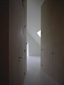 Room with sloping attic ceiling at end of narrow, tapering corridor with integrated doors flush with wood cladding
