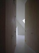 Raum mit Dachschräge am Ende eines eng zulaufenden Flurs mit in Holzverkleidung integrierten Zimmertüren