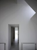Foyer with skylight in sloping roof and view of corridor with light at the end