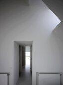 Vorraum mit Oberlicht in der Dachschräge und Blick in Flur mit Licht am Ende