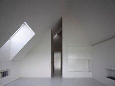 Integrierte Einbauschränke im modernen, weissen Dachraum und Blick in schmalen, hohen Flur mit offener Tür