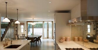Fitted kitchen, island with sink and large dining area in open-plan contemporary living space with retro elements