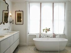 Free-standing bathtub in front of window with roller blinds in elegant bathroom with marble counter and mirror with ornamental frame