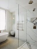 Free-standing bathtub, towel rail and floor-level shower with dramatic marble cladding
