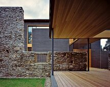 Roofed terrace next to stone wall