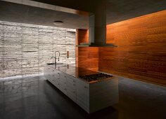 Plain kitchen island in large room with concrete & wood walls