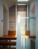 Modern stairwell with slats in front of ceiling-height window and wooden stair treads