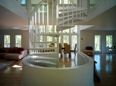 A white spiral staircase in an open-plan living room