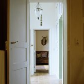 Open doors and view through hallway to hunting trophy on wall