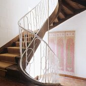 Curved staircase and wall hanging on whitewashed stone wall in traditional stairwell