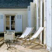 Wooden deckchairs on sunny terrace against Mediterranean house