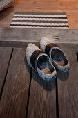 Vintage wooden clogs on board floor in front of open door with doormat