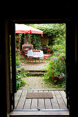 View through open front door into garden with red garden chairs below parasol