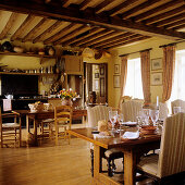 Traditional dining table and open-plan kitchen in rustic dining room with wood-beamed ceiling